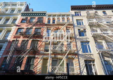 Houses facades with fire escape stairs, sunny day in Soho, New York - Stock Photo
