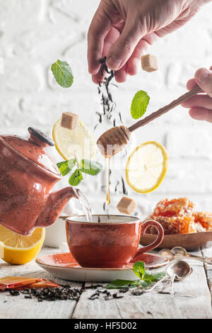 Tea ingredients falling down to the cup on white background. Levitating effect. - Stock Photo