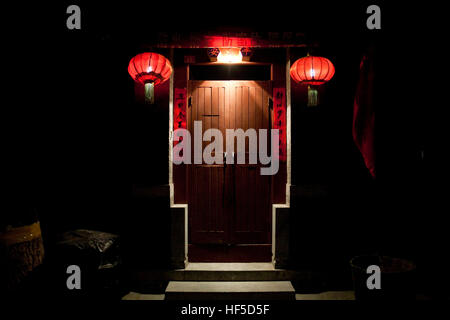A traditional Chinese door  in Beijing at night, in a hutong,  near the Temple of Confucius, decorated for the New - Stock Photo