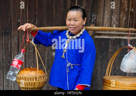 Dong woman carrying baskets,  Chengyang, Sanjiang, Guangxi Province, China - Stock Photo