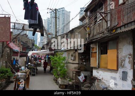 Old residential houses with modern high rise behind, Shanghai, China - Stock Photo