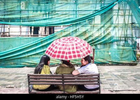 Three young women sharing an umbrella on a bright day in Hanuman Dhoka, Durbar Square, Kathmandu. © Reynold Sumayku - Stock Photo