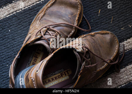 A pair of broken-in deck shoes sitting on an entryway rug. - Stock Photo