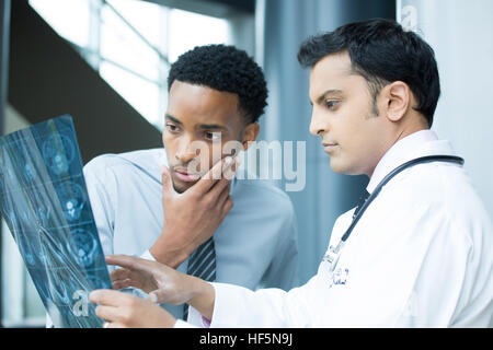 Closeup portrait of intellectual healthcare professionals with white labcoat, looking at full body x-ray radiographic - Stock Photo