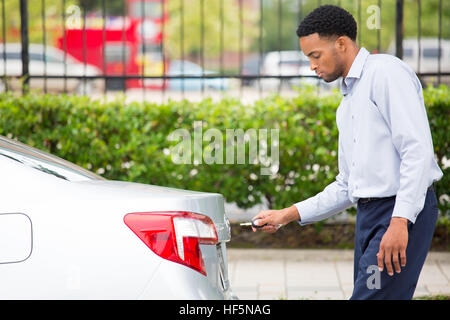 Closeup portrait of a young man trying to open the trunk of his brand new silver car at a parking lot, isolated - Stock Photo