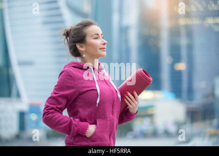 Young sporty woman holding yoga mat - Stock Photo