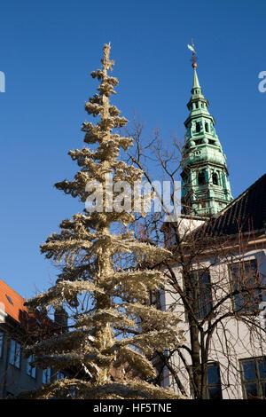 Denmark, Copenhagen, Højbro Plads, Christmas Market, artificial Xmas tree and spire of old Saint Nicolas' church - Stock Photo