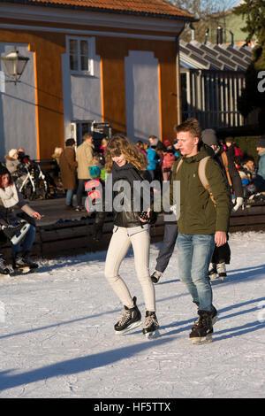Denmark, Copenhagen, Frederiksberg Gardens, couple skating on Christmas public ice rink - Stock Photo