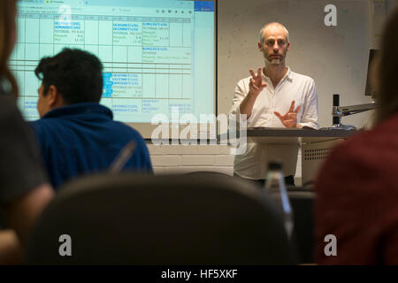 Higher Education in the UK: - a male lecturer leading a class seminar tutorial to undergraduate students in a classroom - Stock Photo