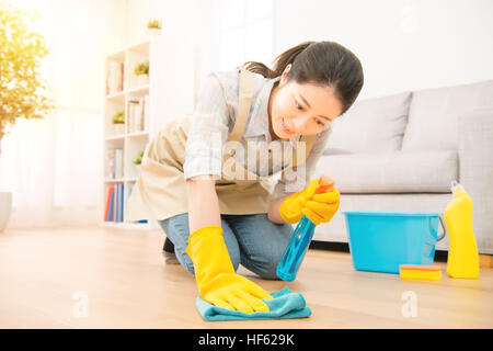 Smiling housewife woman in yellow gloves wash the floor with rag and detergent. mixed race asian chinese model - Stock Photo