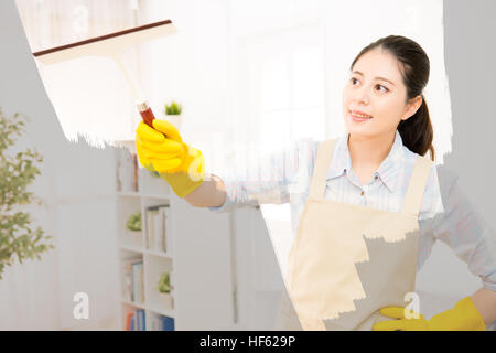 Happy woman in gloves cleaning window with rag at home. Large window glass in foam. Housework concept. mixed race - Stock Photo