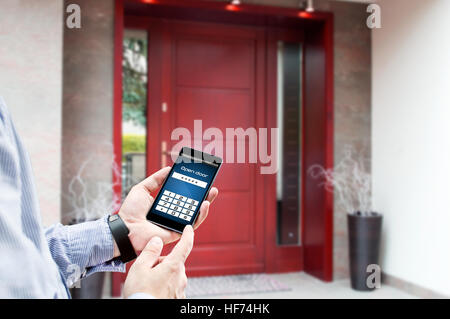 Man uses smartphone to open the door of his house - Stock Photo