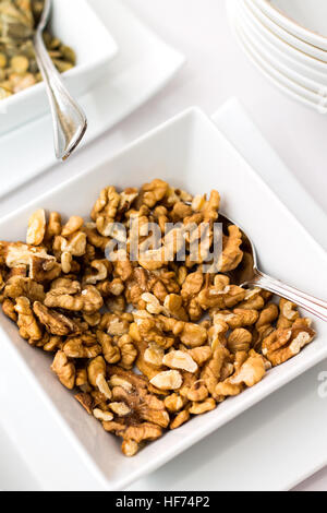 Walnuts in ceramic bowl on table - Stock Photo