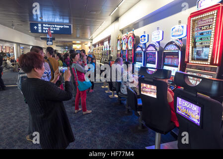 Tourists taking picures of people playing slot machines in the passenger terminal of McCarran International Airport, - Stock Photo