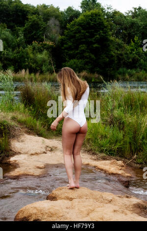 Caucasian Teen Girl Standing At River In White Leotards From Back - Stock Photo