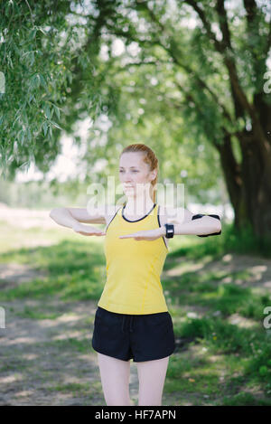 Young fitness woman doing exercise before run. Sportsman standing under tree. - Stock Photo