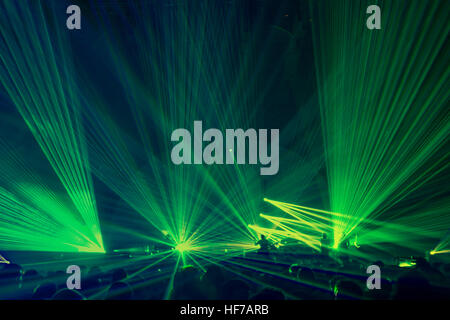 People on the party enjoying concert, dancing in the night club, celebrating new year eve, bright green laser light - Stock Photo