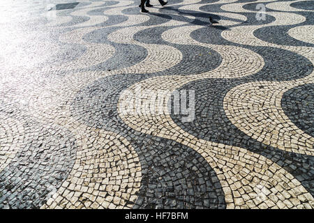 Walking people casting a long shadow on pavement - Stock Photo