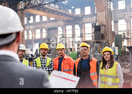 Steel workers listening to manager in meeting in factory - Stock Photo