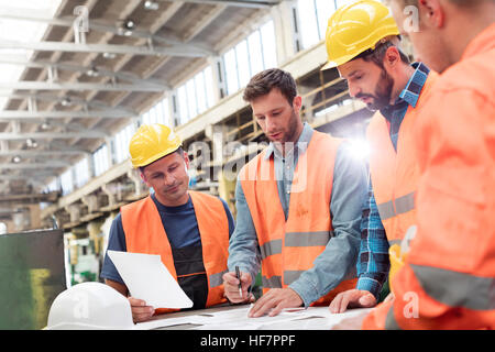 Steel workers and engineers meeting reviewing blueprints in factory - Stock Photo