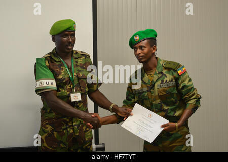 Lt. Col. Joe Kibet Murrey, the AMISOM Force Spokesperson hands over a certificate to a military officer at the end - Stock Photo