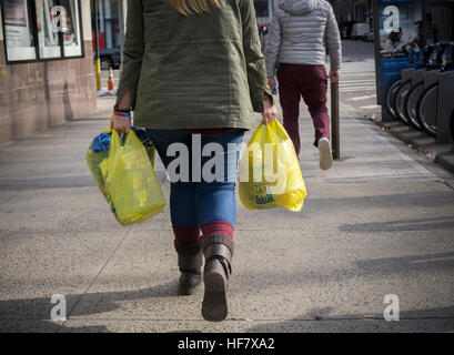 A shopper with her supermarket plastic bags in New York on Friday, December 23, 2016. After a delay earlier this - Stock Photo