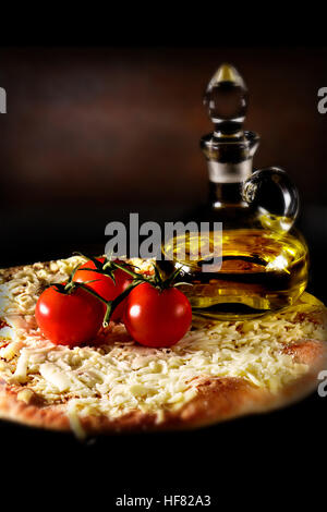 Classic Italian margherita pizza smothered with grated mozzarella cheese and tomato sauce shot against a rustic - Stock Photo