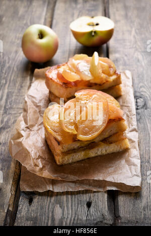 Caramelized apples on toast bread over wooden background - Stock Photo
