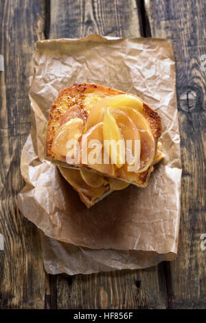 Sweet sandwich with caramelized apples on wooden background, top view