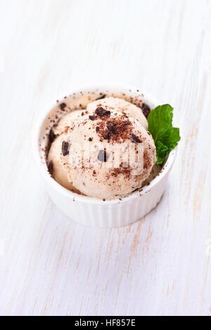 Vanilla ice cream in bowl on white wooden background - Stock Photo