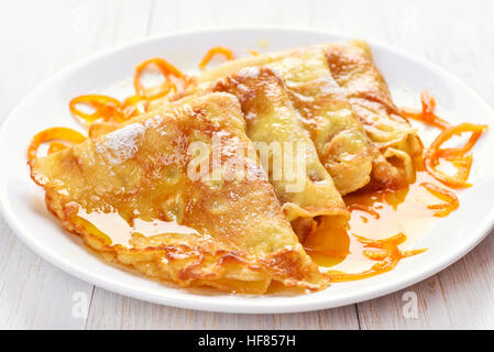Pancakes with orange syrup on white wooden table - Stock Photo