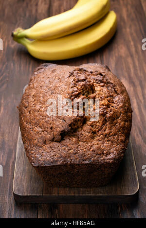 Banana bread loaf on wooden board - Stock Photo