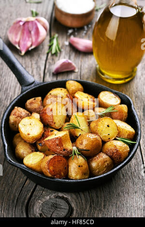 Baked potato in frying pan on wooden background - Stock Photo