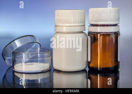 Medicine bottles closeup backlit with blue light on glass - Stock Photo