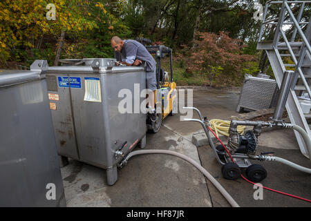Winery worker pumping wine from one tank to another, Bremer Family Winery, Saint Helena, Napa Valley, Napa County, - Stock Photo