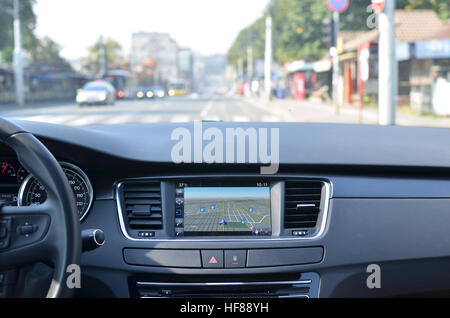 View from inside a car on a part of dashboard with a navigation unit and blurred street in front of a car - Stock Photo