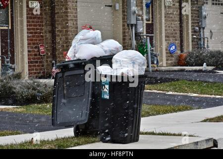 Hanover, Maryland, USA. 30th December, 2016. Trash and recycling bins lay out on street while they are being snowed - Stock Photo