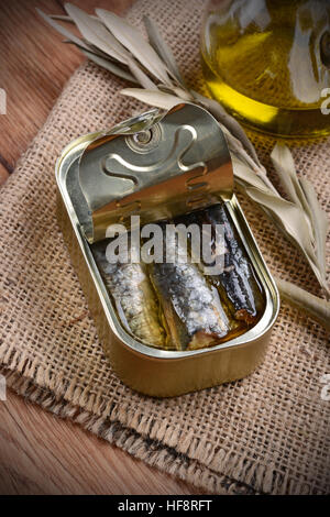 tinned anchovies in oil on the wooden table - Stock Photo