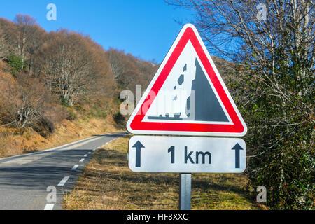 Falling rocks 1km triangular road sign with blue sky - Stock Photo