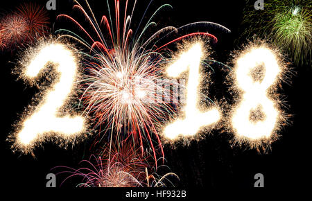 3D rendering of Happy New Year Fireworks with the year 2018 lit up in glowing sparkles and light. - Stock Photo