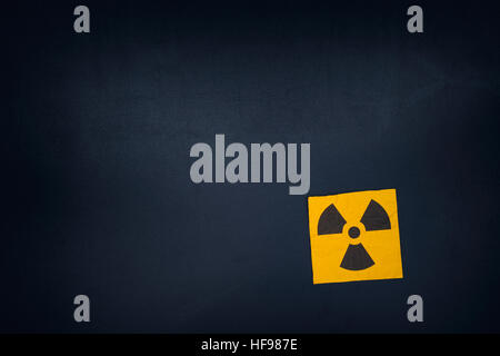 Radiation warning sign on a blackboard. Vignette. - Stock Photo