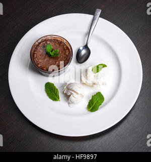 Warm dessert chocolate fondant lava cake served with vanilla ice cream balls and mint on white plate. Famous French - Stock Photo