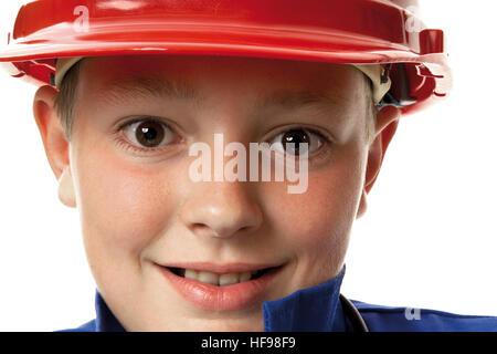 Closeup shot of a young boy wearing a hardhat - Stock Photo