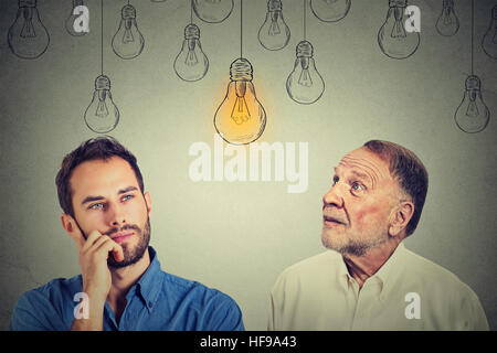 Cognitive skills concept, old man vs young person. Senior man and young guy looking at bright light bulb isolated - Stock Photo