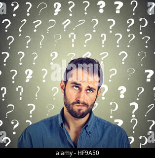 Confused skeptical man thinking looking up puzzled many question marks above head isolated on gray wall background. - Stock Photo
