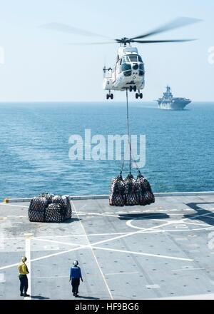An Aerospatiale SA 330J Puma helicopter delivers supplies on the flight deck of the USN San Antonio-class amphibious - Stock Photo