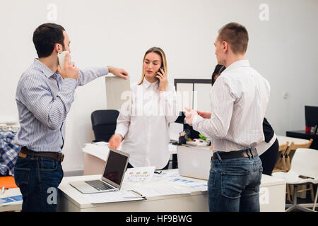 Group of four diverse cheerful co-workers taking self portrait and making funny gestures with hands at small office - Stock Photo