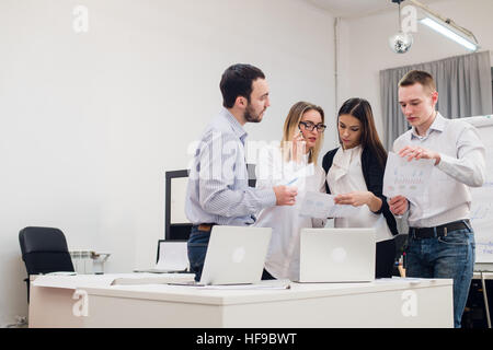 Group of four diverse men and women in casual clothing talking in office - Stock Photo