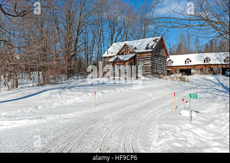 Historic log home in snow - Stock Photo