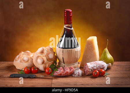 Red wine, bread, cheese and salami on the wooden table - Stock Photo